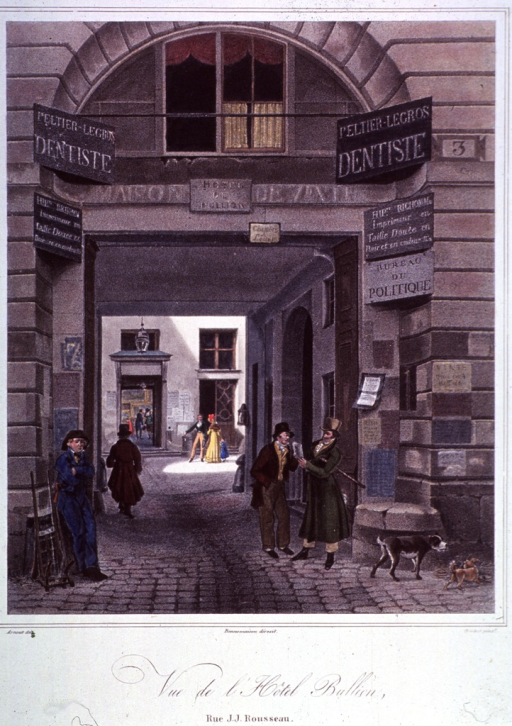 <p>View from a street into a courtyard.  Above the entrance are two dentist's signs.</p>