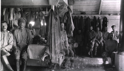 <p>An interior view of a sod barrack with the men sitting on cots and benches.</p>