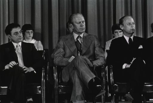 <p>Theodore Cooper, President Gerald R. Ford, and Donald S. Fredrickson are in the Masur Auditorium sitting on chairs with legs crossed.  There is a row of people behind them.  Facial expressions are somber.  It is the inauguration of Dr. Cooper as the assistant secretary for health at the Department of Health, Education, and Welfare (DHEW) and Dr. Fredrickson as the director of the National Institutes of Health (NIH).</p>
