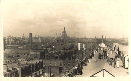 <p>Black and white photograph of an aerial view of the rooftop of King George Military Hospital. London is also seen from an aerial view.  On the roof are many men in military uniform and nurses.</p>