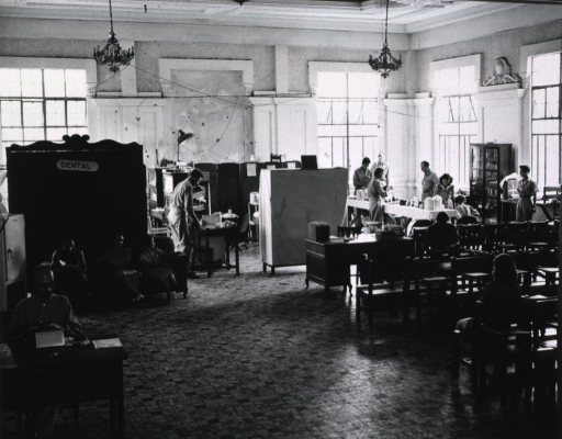 <p>The room is divided into a waiting area, in which chairs are lined up in rows in front of a desk, and a work area.  Men and women either sit in chairs or stand.  In the foreground a man sits at a desk typing.  A makeshift wall in the background has a sign reading &quot;Dental&quot; affixed to it.</p>