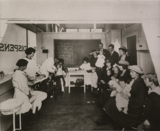 <p>Interior view of outpatient clinic; one side of the room is filled with mothers and children awaiting their turns; a physician examines a young girl and a nurse is recording medical data; a baby is being weighed on the left.</p>
