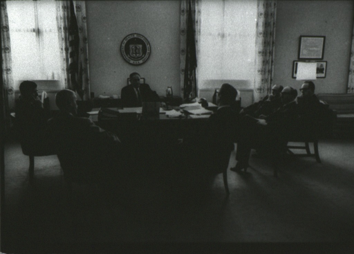 <p>John Gardner and several other men are seated around a desk in an office.</p>