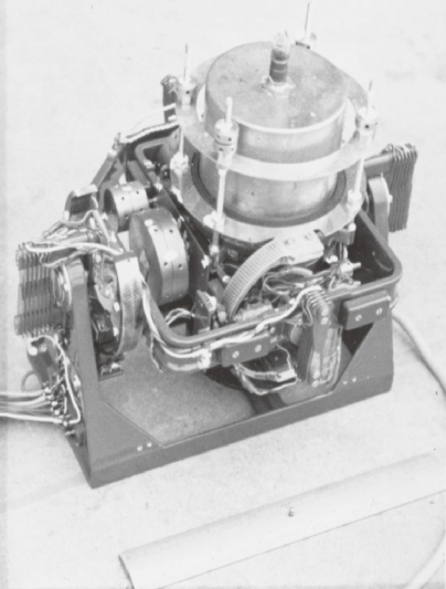 The first model of the string gravity meter TSSG-60. A vertical gyroscope for the horizontal navigation of an airplane was remodeled and the string gravity meter was installed directly on it. The string was placed in an electronically controlled housing of constant temperature. With this gravity meter, we succeeded in measuring gravity at sea from Tokyo to Miyakejima Island in July 1961. Length of the scale in the photograph is 20 cm.