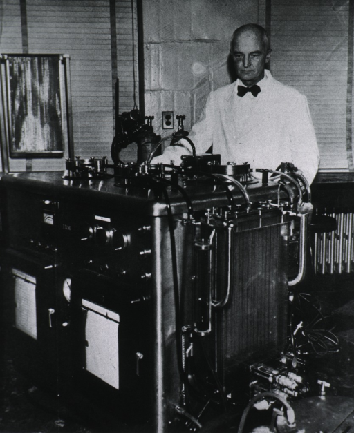 <p>Head and shoulders, full face, standing behind laboratory equipment.</p>