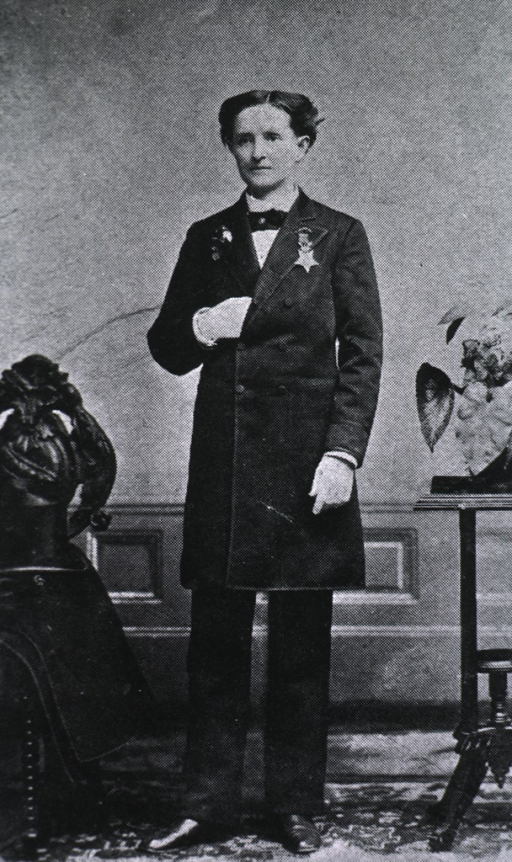 <p>Standing, full length, hand in coat.  Wearing trousers.</p>