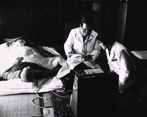 <p>Interior view: a patient is lying on a mat on the floor; kneeling next to him are a physician and a nurse; they are discussing his condition.</p>