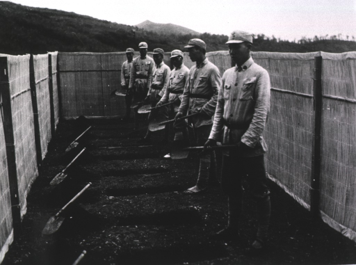 <p>Exterior view: surrounded by a fence, holding shovels, is a row of men standing in front of a row of rectangular holes in the ground.</p>