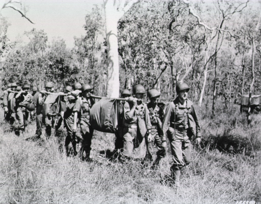 <p>A phalanx of soldiers use carrying poles to transport supplies and equipment in daylight through tall grass and a thicket of trees.</p>