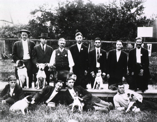 <p>Group portrait of 11 U.S. Public Health Service rat-proofers and their dogs during the New Orleans plague campaign.</p>
