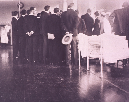 <p>Interior view of ward; a crowd of medical students has gathered around Sir William Osler during bedside consultation.</p>