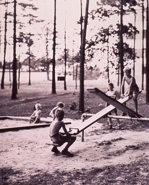 <p>Children are playing on a seesaw and in a sandbox at the playground of a housing project.</p>