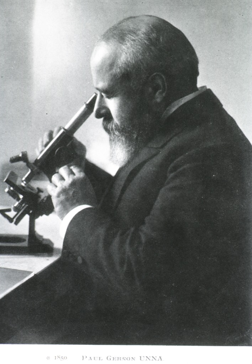 <p>Left profile, seated, looking into microscope.</p>