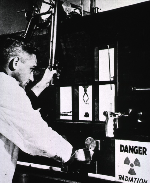 <p>A man is manipulating mechanical arms used for handling radioactive materials to prevent human exposure to radiation.</p>