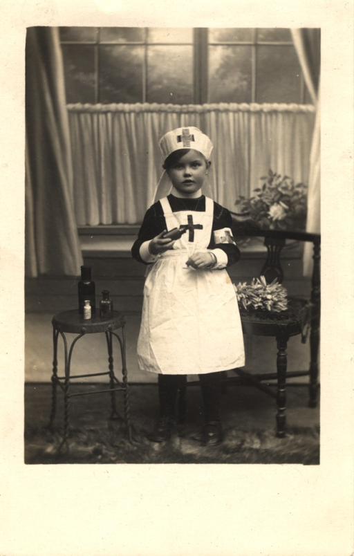 <p>Black and white photograph of a little girl wearing a Red Cross nurse uniform. She is holding a medicine bottle in her right hand. To her right is a stool on which there are 3 medicine bottles of varying sizes.  To her left is a wooden chair with a plant.  Behind her is a window partially obscured by curtains. There is a vase with flowers on the window sill.</p>