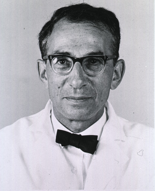 <p>Head and shoulders, full face, wearing lab jacket and glasses.</p>