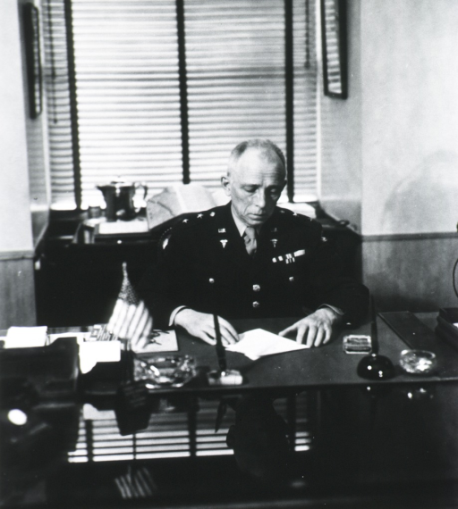 <p>Half-length, seated at desk, front pose; reading papers on desk; wearing uniform.</p>