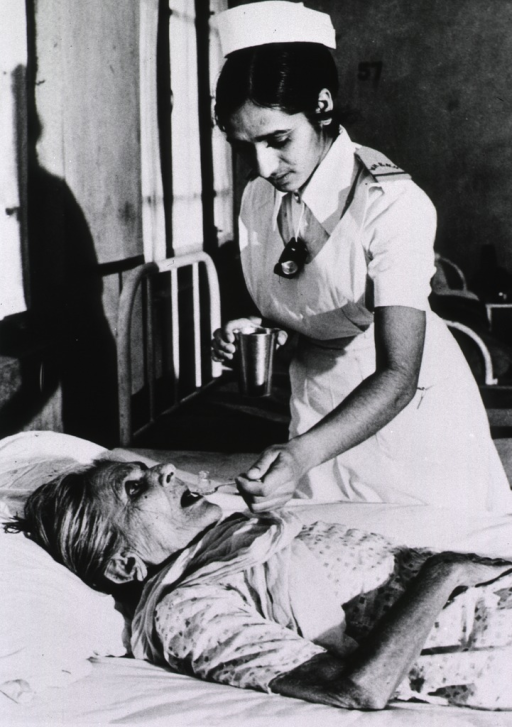 <p>Interior view: a nurse is administering medication by the spoonful to an elderly woman lying on her back.</p>
