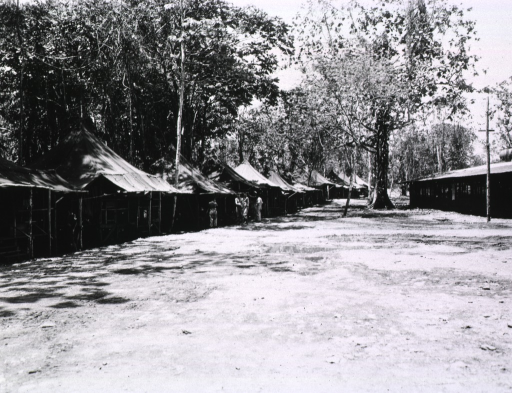 <p>Subect:  Servicemen stand next to a row of open-air tents.</p>
