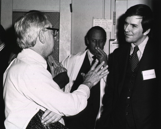 <p>Secretary David Mathews, of the Department of Health, Education, and Welfare (DHEW) is listening to Nobel Laureate Julius Axelrod of the National Institute of Mental Health (NIMH).  Dr. Fredrickson is leaning against the wall observing the conversation.  A third man, only partially visible in the photo, is standing next to Dr. Axelrod.  There is a clipboard on a door to Dr. Fredrickson's left and a notecard taped to the wall.  The door to Dr. Fredrickson's right has wire mesh in the window.</p>