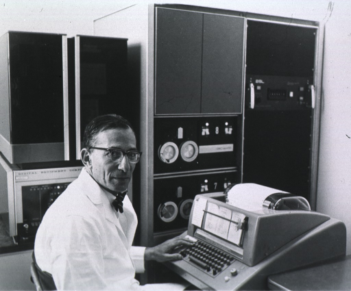 <p>Half-length, body turned to right, head slightly to right, wearing lab coat and glasses, in lab using equipment.</p>