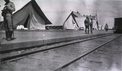 <p>Soldiers(?) stand near the railroad of a Military Mobile Hsopital; tents are pitched nearby.</p>