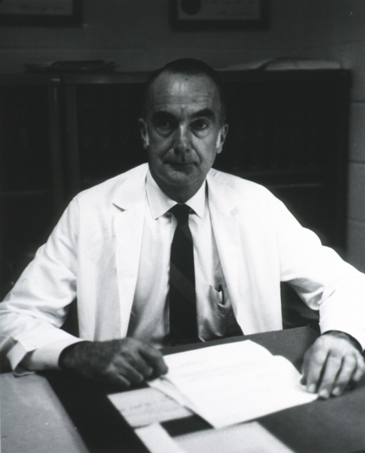 <p>Half length, full face, wearing lab coat; seated at desk.</p>