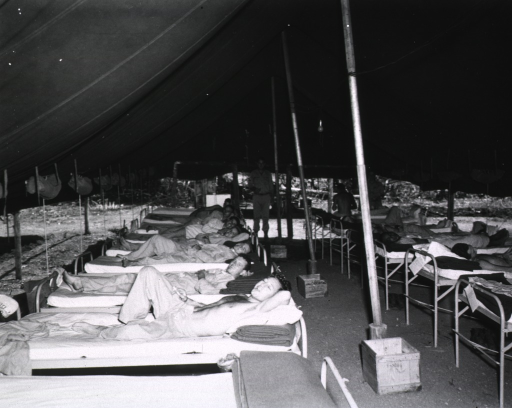 <p>Servicemen lie in two rows of beds in a tent.</p>