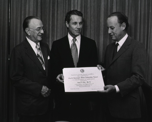 <p>Karl Piez and Donald S. Fredrickson are holding a certificate for the G. Burroughs Mider lecturership.  G. Burroughs Mider is standing to Dr. Piez's left.  The certificate reads: Department of Health, Education, and Welfare, Public Health Service, the G. Burroughs Mider Lectureship Award, to a National Institutes of Health Scientist, presented to, Karl A. Piez, Ph.D., in Recognition and Appreciation of; Outstanding Contributions to; Biomedical Research.</p>