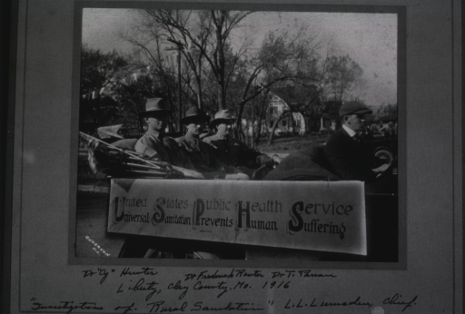 <p>Three men wearing hats sit in the back of an open-topped car; a sign on the side of the car reads: United States Public Health Service - Universal Sanitation Prevents Human Suffering.</p>