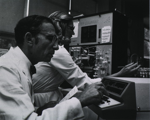 <p>Half-length, right profile, wearing glasses, using input apparatus to transfer blood test results to computer, lab lech. is running blood tests in bachground (on Coulter Counter).  In lab at Clinical Laboratories, UCSF.</p>
