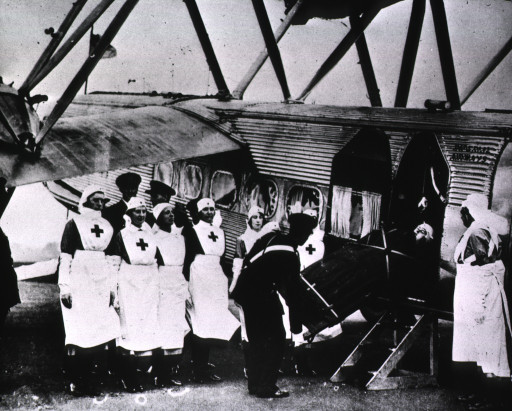 <p>A group of nurses are standing next to an airplane as a patient is being carried aboard on a stretcher.</p>