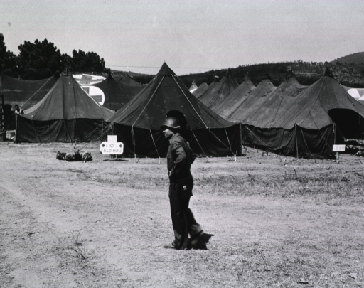 <p>A serviceman in uniform walks across a field.  In the background is a group of tents.  A sign reading &quot;10 Field Hospital&quot; is posted in front of one of the tents (cf. Photograph no. 2 in this series).</p>