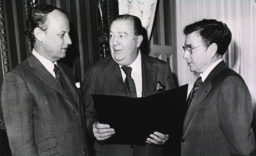 <p>Jennings Randolph, the U.S. senator from West Virginia, is speaking with Donald S. Fredrickson, director of the National Institutes of Health (NIH) and Theodore Cooper, assistant secretary of the Department of Health, Education, and Welfare (DHEW).  Senator Jennings is holding a black folder.</p>