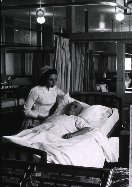 <p>Interior view: a nurse is standing at the bedside of an elderly patient.</p>