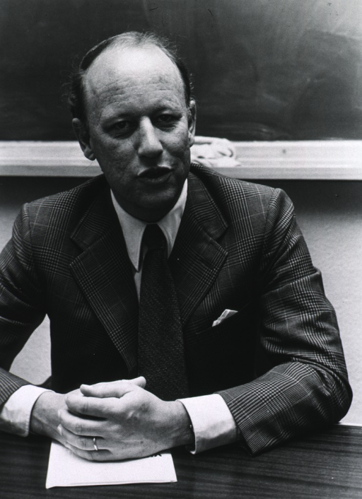 <p>Donald S. Fredrickson is in Madrid, seated at a desk with hands folded over what appears to be a booklet or papers.  A blackboard is behind him.</p>