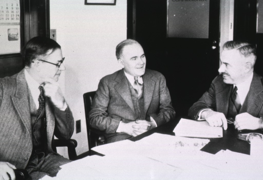 <p>Three men seated at a desk covered with papers.</p>