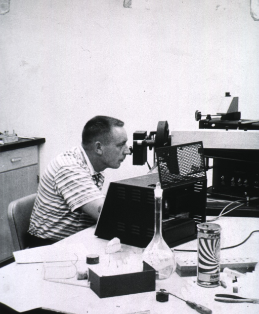 <p>Half-length, seated in laboratory, right profile; using lab equipment similar to spectophotometer.</p>