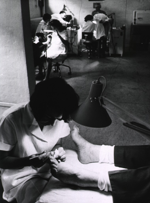 <p>Interior view: a female podiatrist is treating a foot ailment of a patient; a similar scene is repeated in the background.</p>