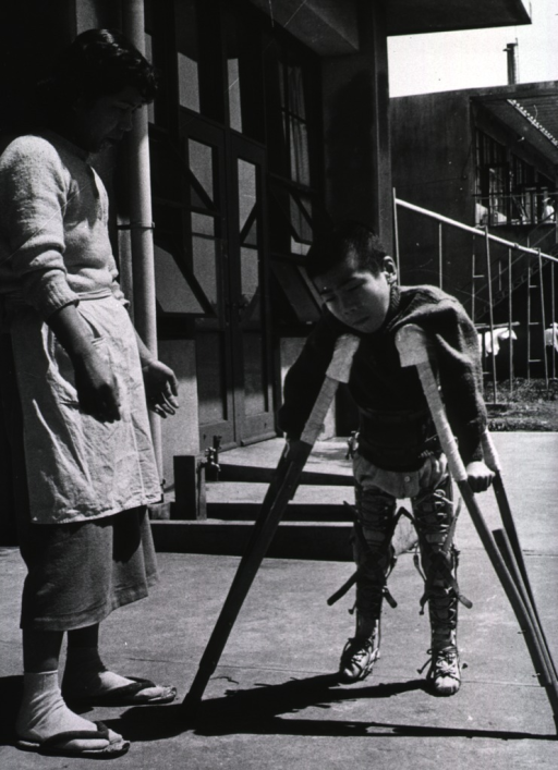<p>A nurse is ready to offer assistance to a young boy struggling to walk with the aid of crutches and leg braces.</p>