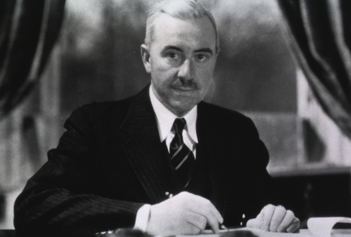 <p>Head and shoulders, seated at desk, full face, arms resting on desk, holding a pencil in right hand.</p>