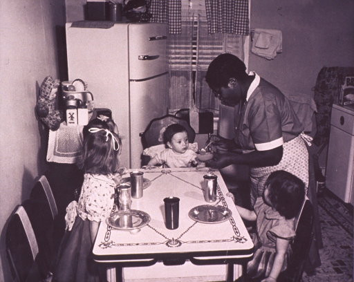 <p>An African American woman is preparing a meal for three white children.</p>