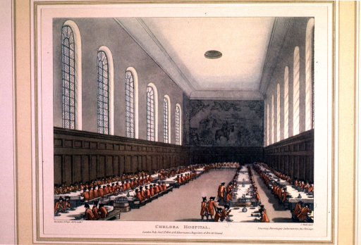 <p>Interior view of the dining hall of the hospital.  Men in black tricorns and red jackets sit and dine at long tables in a high-ceilnged great hall.  A tapestry or mural appears on the back wall.</p>