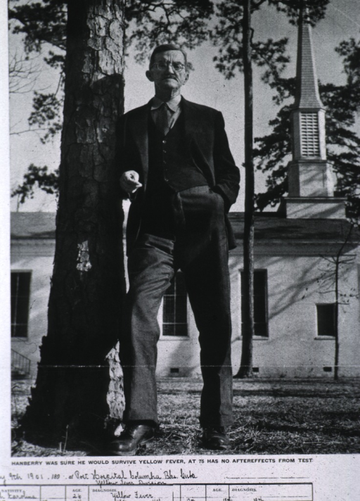 <p>Full length, full face; leaning against a tree; church in background.</p>
