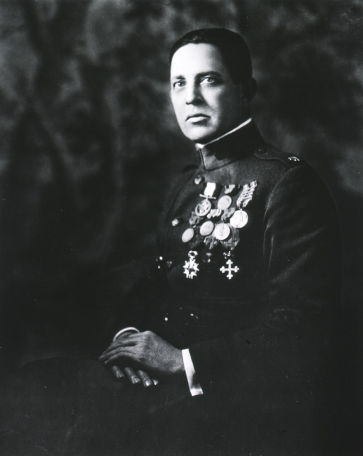 <p>Three-quarter length, seated, left pose, full face; wearing uniform with several medals.</p>