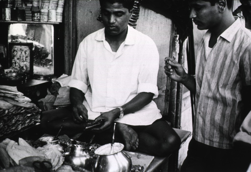 <p>A street vendor preparing &quot;pan&quot; (betel leaves slacked with lime and mixed with other ingredients).</p>