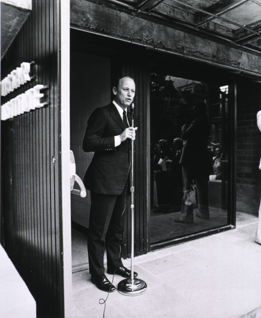 <p>Dr. Fredrickson is standing before a microphone at an open doorway.  &quot;Wistar Institute&quot; is lettered on the door.  The window adjacent to Dr. Fredrickson reflects a man with a movie camera, a gathered crowd, a carry-all bag, and buildings on a hill.  The roof over the extended steps is held by a concrete beam that is somewhat worn.</p>