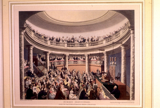 <p>A man lectures at the podium set on a dais in a rotunda-like auditorium.  A crowd of well-dressed men and women sits in rapt attention on floor seats and in loges.  Others stand along an upper balcony and look down.</p>