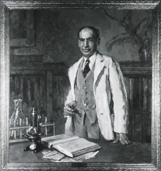 <p>Standing at laboratory table, white coat, holding pipe.</p>