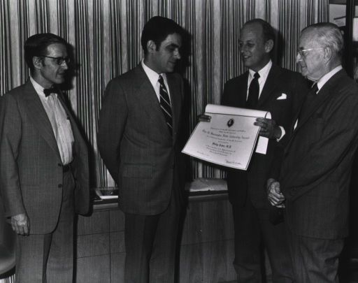 <p>Drs. James Sidbury and G. Burroughs Mider look on as Philip Leder, director of the Laboratory for Molecular Genetics, is presented the G. Burroughs Mider Lectureship Award by Donald S. Fredrickson, director of the National Institutes of Health.  They are standing in front of a stage curtain and a credenza.  A book shelf is behind Dr. Mider.</p>